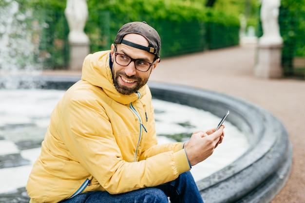 Lateralmente retrato ao ar livre do alegre homem estiloso barbudo de jaqueta amarela e óculos sentado perto da fonte no parque segurando moderno decive nas mãos