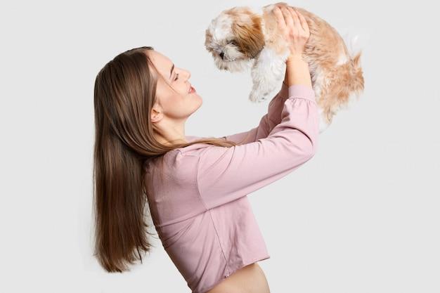 Lateralmente satisfeito mulher de cabelo escuro mantém sua amiga de quatro pernas no ar, brinca com cão de raça, goza de tempo livre, vestido com top elegante, isolado no branco. animais
