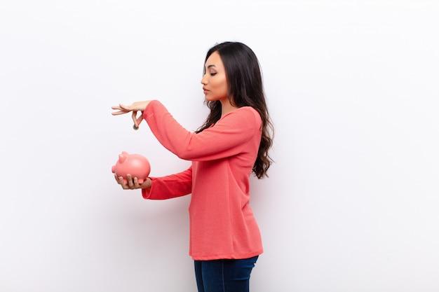 Latina bonita jovem contra a parede plana com um cofrinho