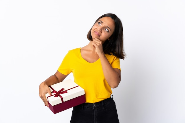 Latina jovem segurando um presente isolado no branco e olhando para cima