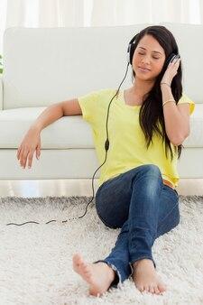 Latina linda curtindo música enquanto está sentado no chão