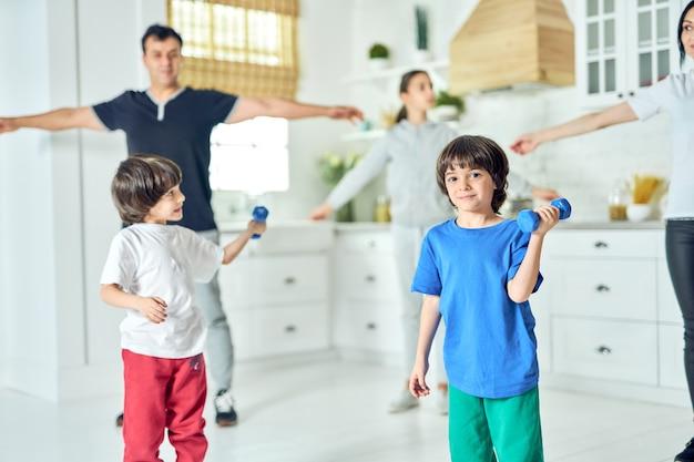 Latino menino bonitinho sorrindo para a câmera, exercitando-se com halteres enquanto trabalhava junto com seus pais e irmãos em casa. família, conceito de estilo de vida saudável. foco seletivo