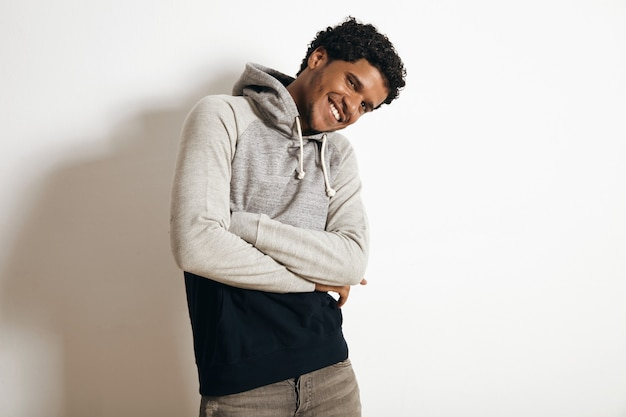 Latino sorridente e feliz usa um suéter preto cinza em branco com capuz e jeans desgastados, cruzando as mãos no peito