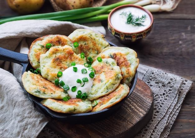 Latkes de panquecas de batata frita caseira fresca em frigideira de ferro em madeira rústica. comida judaica tradicional para a celebração de hannukah.