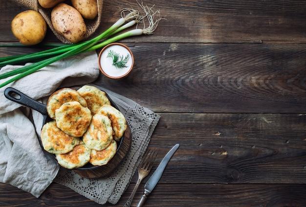 Latkes de panquecas de batata frita caseira fresca na frigideira de ferro na mesa de madeira rústica. vista superior com