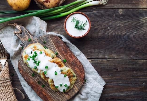 Latkes de panquecas de batata fritas caseiras frescas na tábua de madeira rústica. comida judaica tradicional para a celebração de hannukah. vista do topo.