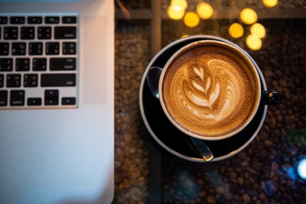 Latte art café em copo preto com computador portátil na mesa, tom escuro