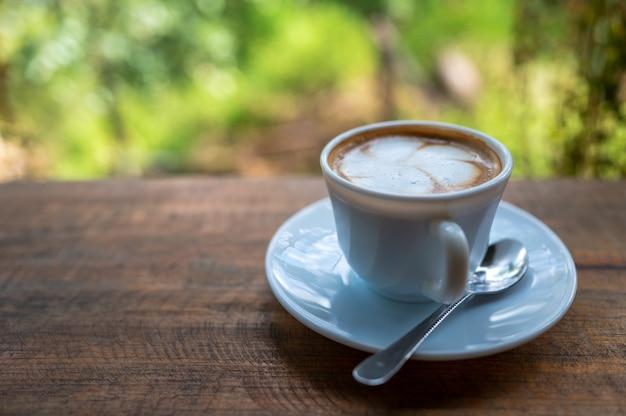 Latte art café na mesa de madeira com bokeh de árvores