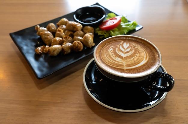 Latte art em copo preto com lanche na mesa de madeira