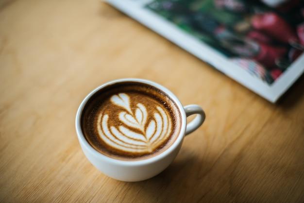 Latte art em xícara de café na mesa de café