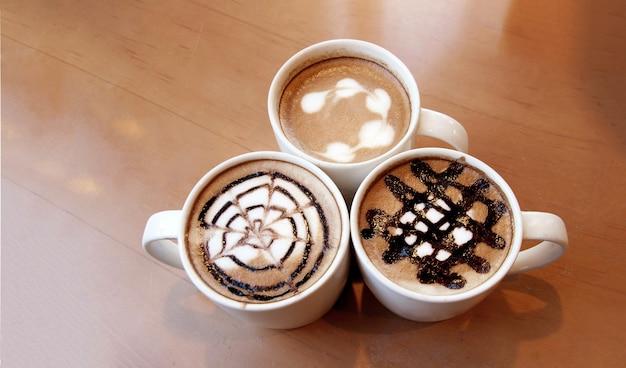 Latte art em xícara de café na mesa de madeira