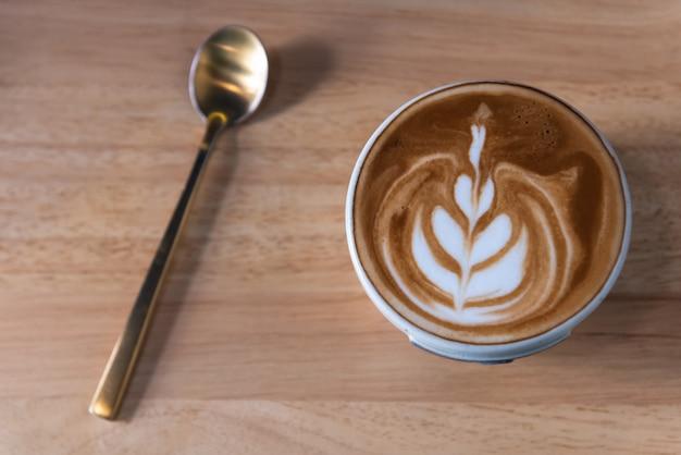 Latte art xícara de café em forma de coração, cobertura e colher na placa de madeira