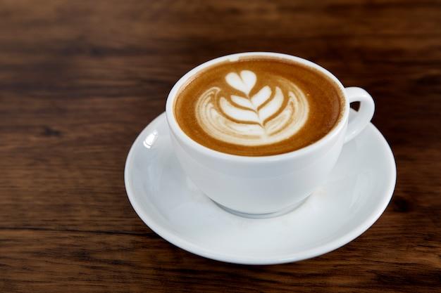 Latte coffee art na mesa de madeira