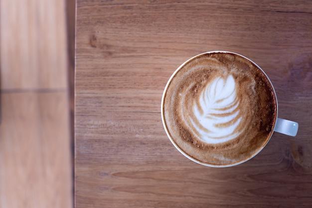 Latte da xícara de café na tabela de madeira.