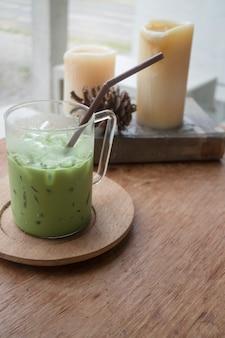 Latte de chá verde gelado na mesa de madeira