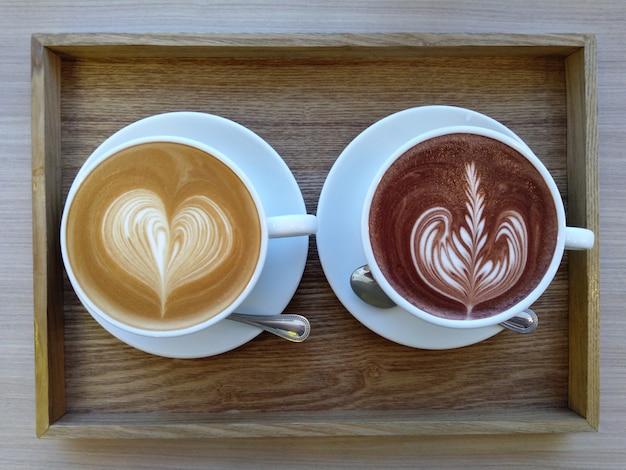 Latte e cacau quentes nos copos brancos na tabela de madeira na cafetaria.
