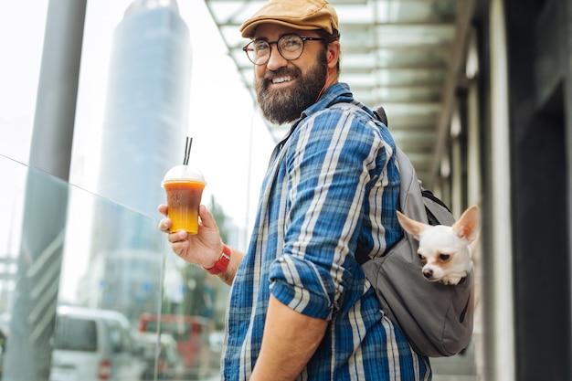Latte gelado. homem bonito e sorridente bebendo café com leite gelado do lado de fora do shopping enquanto vai lá com seu cachorrinho