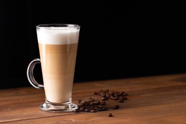 Latte macchiato em copo de vidro com alça com café isolado em fundo de madeira