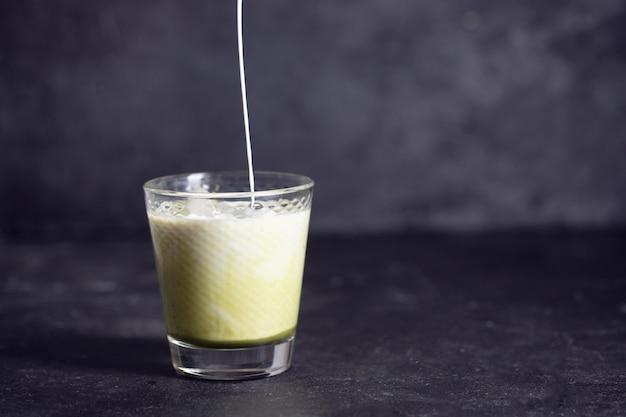 Latte matcha verde com derramamento de leite em um fundo preto com spase de cópia