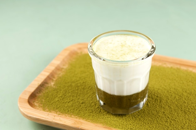 Latte matcha verde quente com leite de amêndoa em uma travessa de bambu.