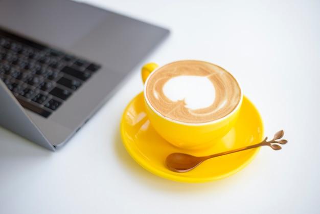 Latte quente arte em copo amarelo na mesa de trabalho