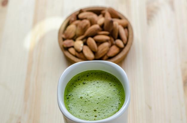 Latte quente de chá verde em tempo preguiçoso com nozes amêndoas