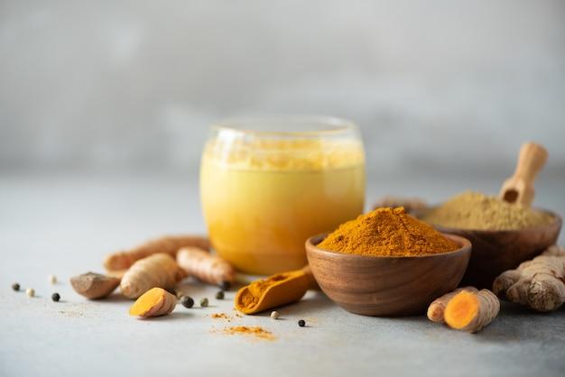Latte saudável da cúrcuma do vegetariano ou leite dourado, raiz de cúrcuma, pó do gengibre, pimenta preta sobre o fundo concreto cinzento.