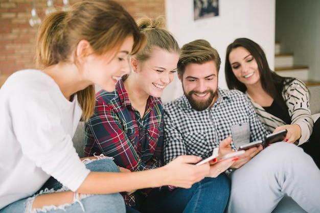 Laughing amigos usando dispositivos sentados no sofá