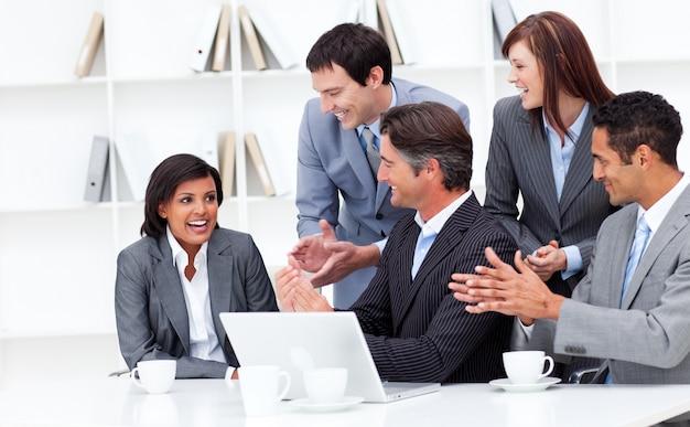 Laughing businesswoman aplaudiu por sua equipe