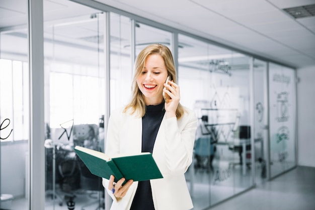 Laughing businesswoman with book