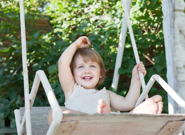 Laughing girl on swing
