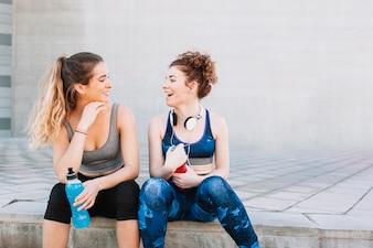 Laughing girls in sportswear sentado na rua