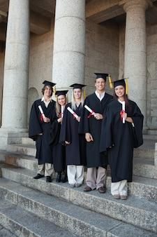 Laughing graduates posando o thumb-up