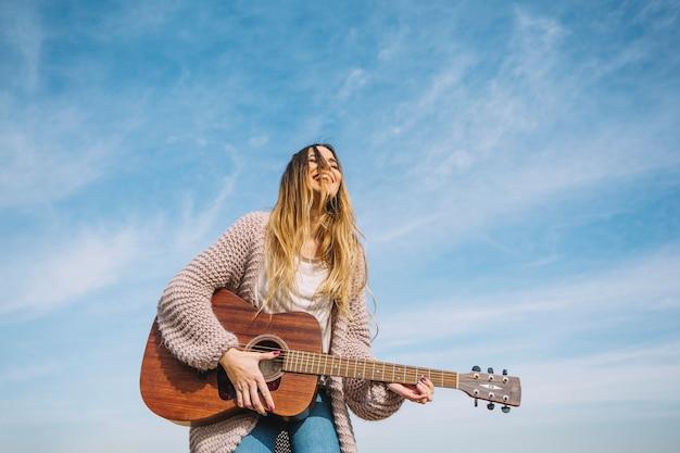 Laughing mulher tocando guitarra na natureza Foto Premium