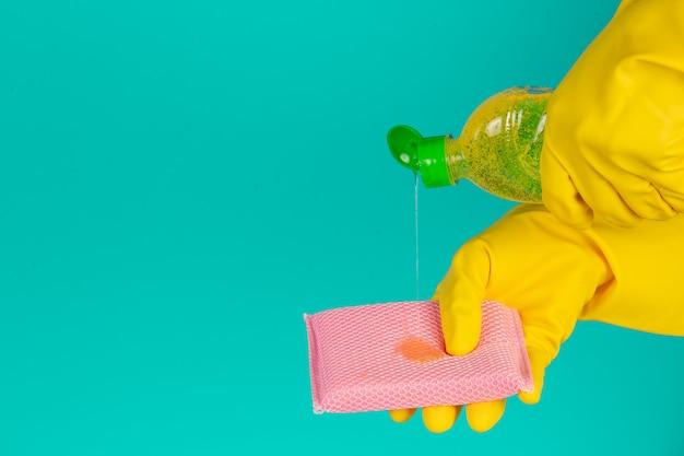 Lava-louças com luvas amarelas em azul.