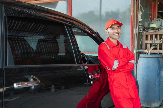 Lavador de carros asiático com uniforme vermelho em pé sorrindo encostado no carro no lava-rápido