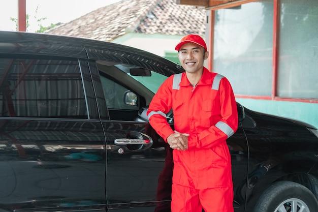 Lavador de carros asiático vestindo uniforme vermelho sorrindo encostado no carro após terminar de lavar o carro no trabalho