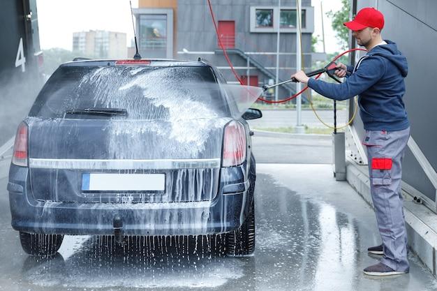 Lavador de carros profissional está lavando o carro do cliente