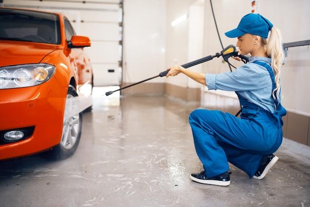 Lavadora de uniforme limpa a roda com pistola de alta pressão nas mãos