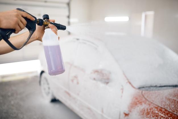 Lavadora fêmea aplica espuma no automóvel