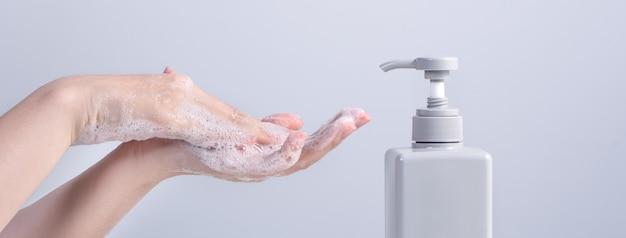Lavagem das mãos. mulher jovem asiática usando sabonete para lavar as mãos, conceito de higiene para parar de espalhar o coronavírus isolado no fundo branco cinza, close-up.