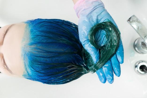 Lavagem de cabelo feminino com shampoo condicionador na pia com ducha especial
