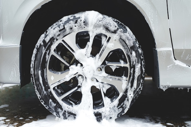 Lavagem de carro com sabonete de espuma ativa. limpeza do pneu da roda. conceito de serviço de limpeza comercial.