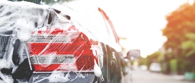 Lavagem de carros ao ar livre com sabonete de espuma ativa. conceito de serviço de lavagem de limpeza comercial.