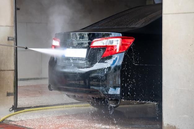 Lavagem de carros. limpando o carro com água em alta pressão e espuma. transporte