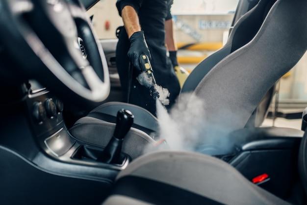 Lavagem de carros, trabalhador limpa assentos com limpador a vapor