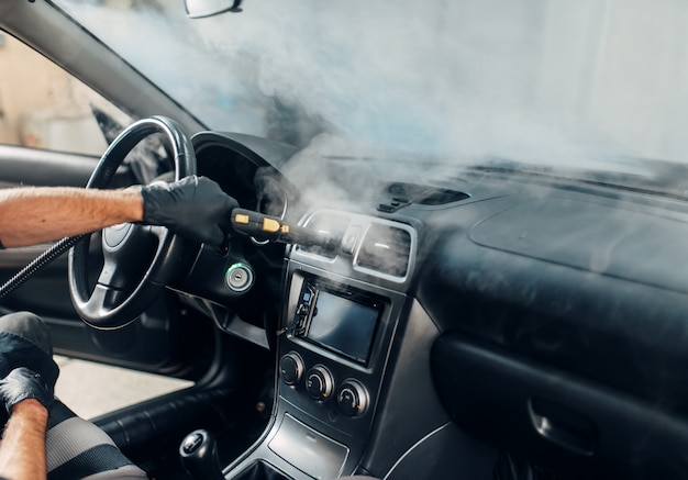 Lavagem de carros, trabalhador limpa salão com limpador a vapor