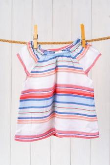 Lavagem de roupas de bebê presas a uma corda para secar