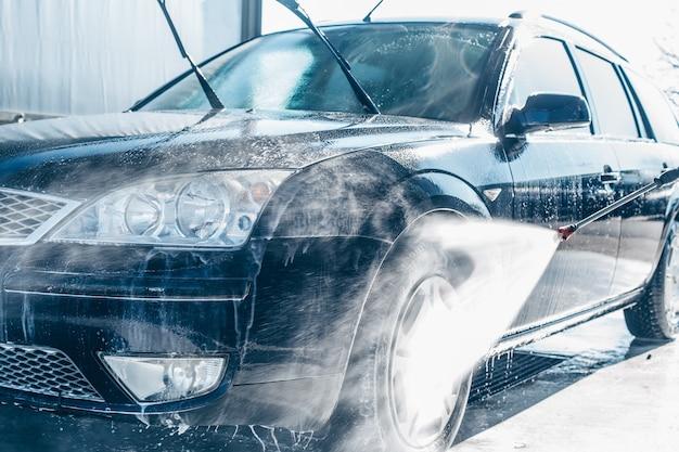 Lavagem manual de carros, limpeza com água de alta pressão na lavagem de carros, conceito de purificação