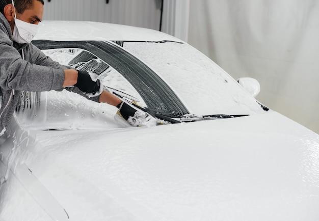Lavagem moderna com espuma e água a alta pressão de um carro branco. lava-jato.